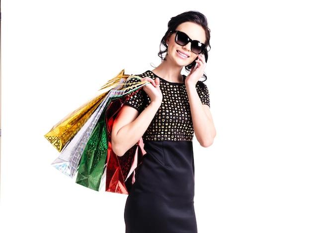 Porträt der lächelnden eleganten frau im schwarzen kleid mit einkaufstaschen, die auf dem handy sprechen - lokalisiert auf weiß.