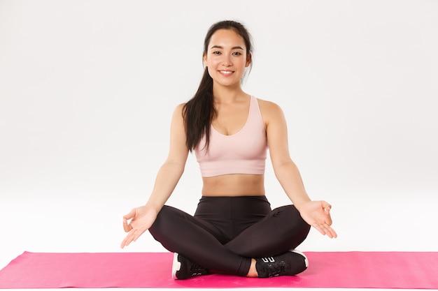 Porträt der lächelnden, entspannten und ruhigen asiatischen brünette mit perfektem körper, glücklich aussehend, in lotushaltung sitzend, gekreuzte beine auf gummimatte für fitness- oder yogaübungen, meditierend