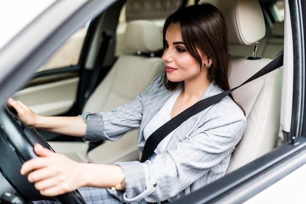 Porträt der lächelnden fahrerfrau, die ihren sicherheitsgurt vor dem fahren eines autos anschnallt.