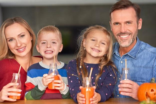 Porträt der lächelnden familie, die smoothie trinkt