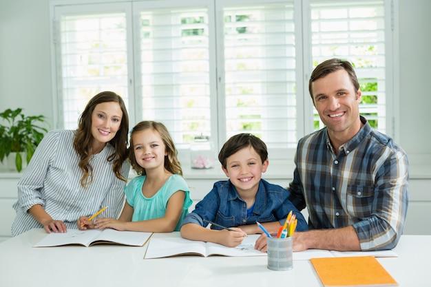 Porträt der lächelnden familie, die zusammen im wohnzimmer studiert