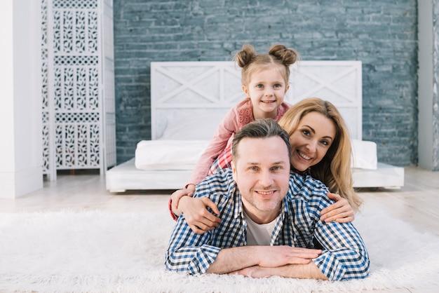 Porträt der lächelnden familie liegend auf einander im schlafzimmer