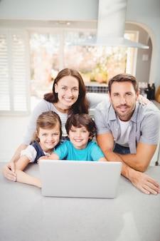 Porträt der lächelnden familie mit laptop auf tabelle
