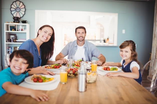 Porträt der lächelnden familie mit lebensmittel auf speisetische