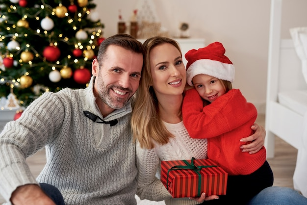 Porträt der lächelnden familie mit weihnachtsgeschenk