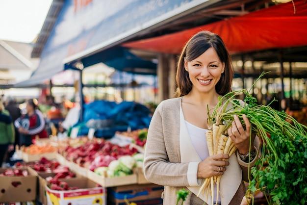 Porträt der lächelnden frau am kaufenden gemüse des grünen marktes.