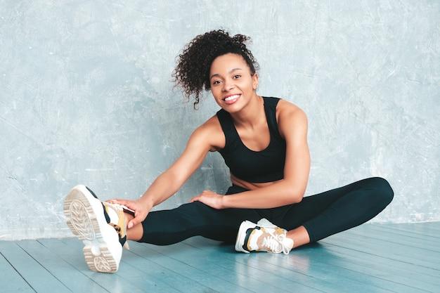 Porträt der lächelnden frau der eignung in der sportkleidung mit afrolockenfrisur