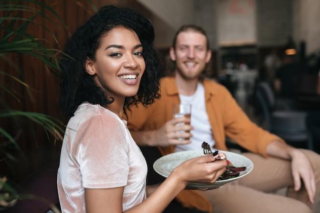 Porträt der lächelnden frau, die am restaurant mit freund sitzt