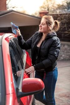 Porträt der lächelnden frau, die auto mit lappen poliert