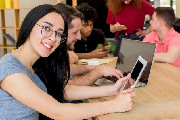 Porträt der lächelnden frau die digitale tablette halten, die kamera beim sitzen neben ihren freunden betrachtet, die elektronische geräte und buch auf hölzernem schreibtisch verwenden