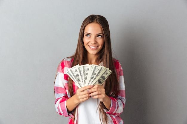 Porträt der lächelnden frau, die dollars hält