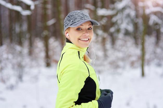 Porträt der lächelnden frau, die in der winterzeit läuft