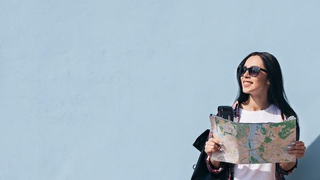 Porträt der lächelnden frau die karte halten, die gegen die blaue wand steht, die weg schaut