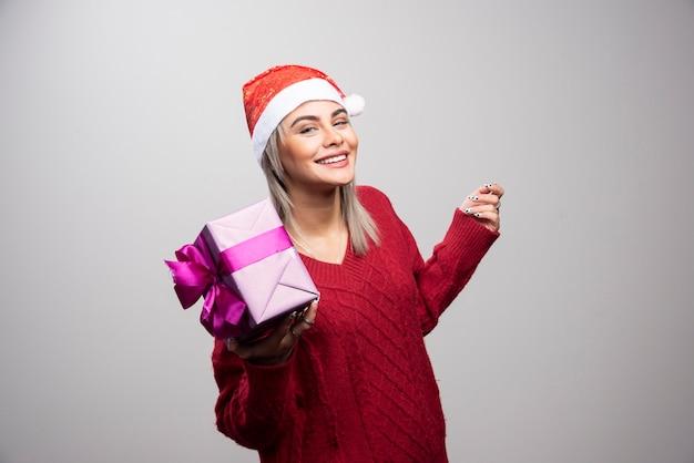 Porträt der lächelnden frau, die mit weihnachtsgeschenk auf grauem hintergrund aufwirft.