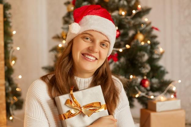 Porträt der lächelnden frau, die neujahrsgeschenk im kasten mit goldband hält