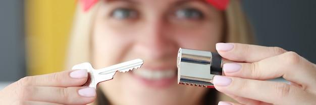 Porträt der lächelnden frau, die schloss und schlüssel in ihren händen hält