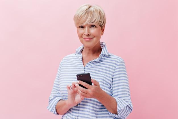 Porträt der lächelnden frau, die smartphone auf rosa hintergrund hält