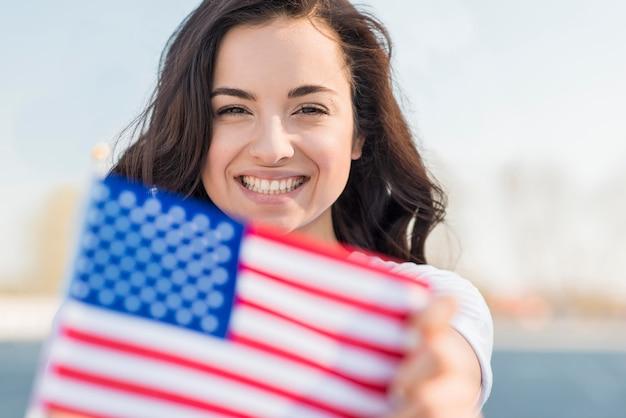 Porträt der lächelnden frau, die usa-flagge hält