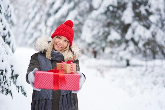 Porträt der lächelnden frau, die zwei weihnachtsgeschenke gibt