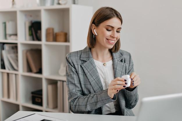 Porträt der lächelnden frau im büro-outfit, das airpods anzieht, um mit kunden zu kommunizieren.