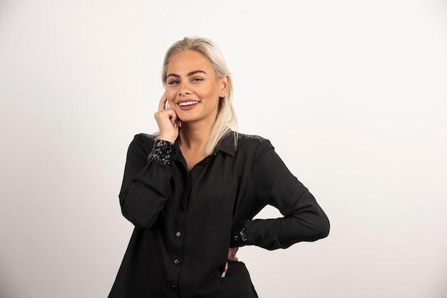 Porträt der lächelnden frau im schwarzen hemd, das auf weißem hintergrund aufwirft. hochwertiges foto