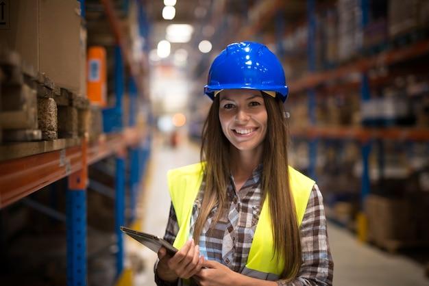 Porträt der lächelnden frau in der schutzuniform mit helm, der tablette im lagerzentrum hält