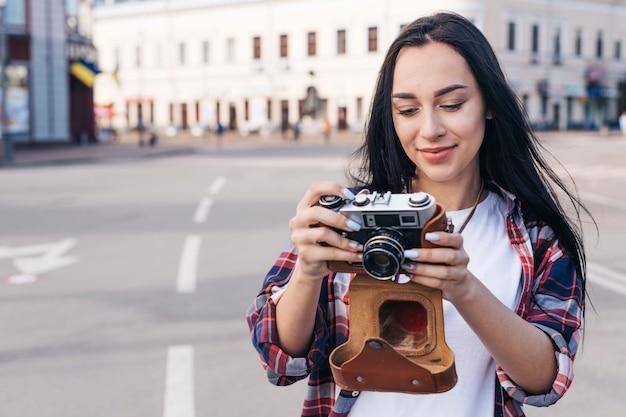 Porträt der lächelnden frau kamera auf straße betrachtend