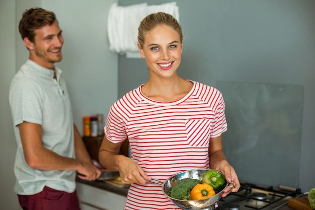 Porträt der lächelnden frau lebensmittel mit ehemann kochend