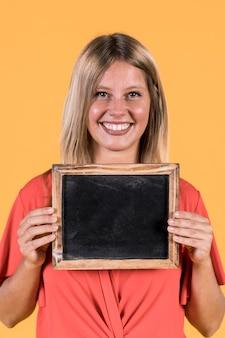 Porträt der lächelnden frau leeren schwarzen schiefer halten