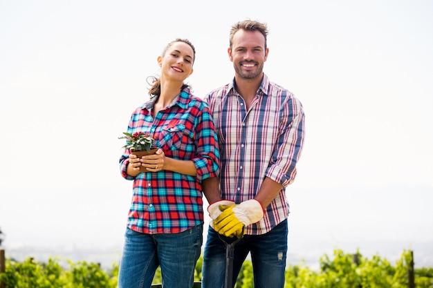 Porträt der lächelnden frau mit dem mann, der topfpflanze hält
