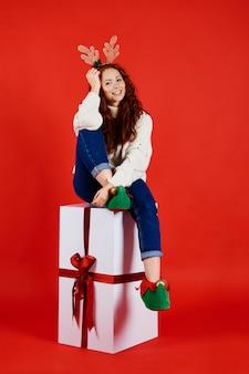 Porträt der lächelnden frau mit dem riesigen weihnachtsgeschenk
