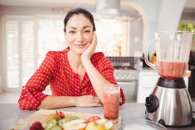 Porträt der lächelnden frau mit fruchtsaft auf tabelle