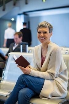 Porträt der lächelnden frau mit pass, der im wartebereich sitzt