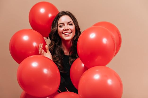 Porträt der lächelnden frau mit welligem dunklem haar, das mit riesigen luftballons auf beigem hintergrund aufwirft.