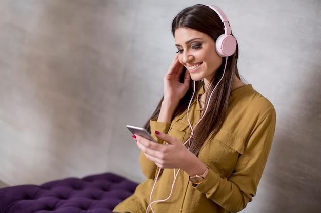 Porträt der lächelnden frau musik auf kopfhörer sitzend und hörend