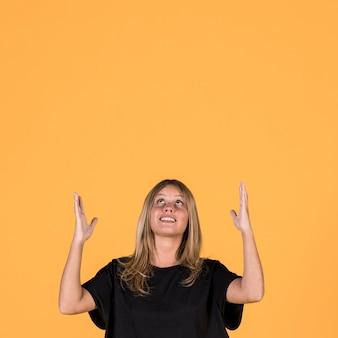 Porträt der lächelnden frau oben schauend und auf gelben wandhintergrund gestikulierend