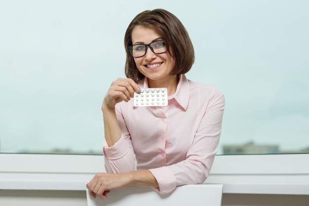 Porträt der lächelnden frau pille halten