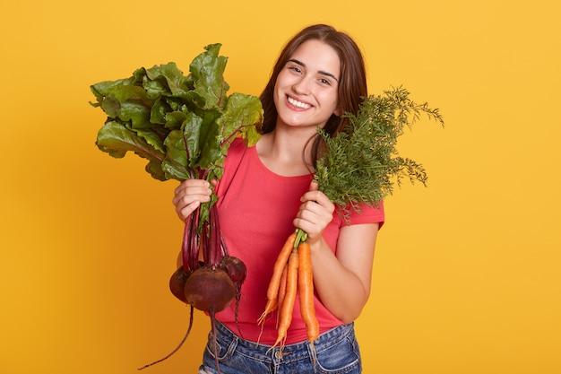 Porträt der lächelnden gärtnerin mit karotte und rote beete in den händen