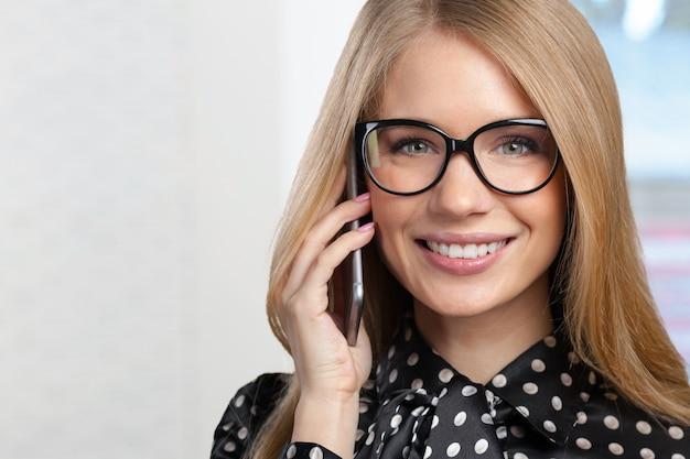 Porträt der lächelnden geschäftsfrau, die das telefon spricht