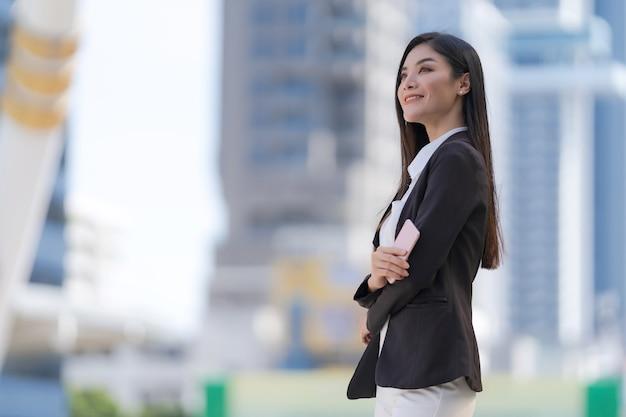 Porträt der lächelnden geschäftsfrau, die ein telefon hält, das vor modernen bürogebäuden steht