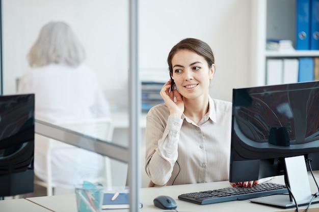 Porträt der lächelnden geschäftsfrau, die headset trägt, während sie als call-center-betreiber im büroinnenraum arbeitet