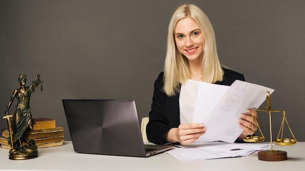 Porträt der lächelnden geschäftsfrau, die kamera betrachtet und beim arbeiten im büro lächelt