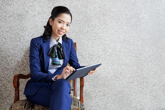 Porträt der lächelnden geschäftsfrau gesetzt auf stuhl mit tablet-pc