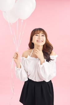 Porträt der lächelnden glücklichen dame mit luftballons auf rosa hintergrund