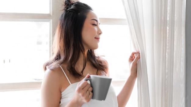 Porträt der lächelnden glücklichen fröhlichen schönen hübschen asiatischen frau, die das trinken und das betrachten der tasse heißen kaffees oder des tees entspannt. mädchen, das gefällt, genießt das frühstücken im ferienmorgenurlaub auf dem bett zu hause