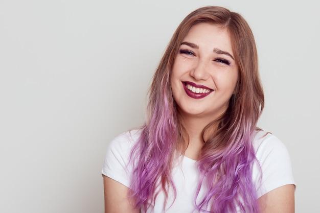 Porträt der lächelnden glücklichen jungen frau, die weißes t-shirt trägt, das kamera mit positivem ausdruck und zahnigem lächeln betrachtet, lokalisiert über grauem hintergrund.