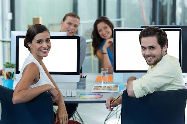 Porträt der lächelnden grafikdesigner, die am schreibtisch sitzen
