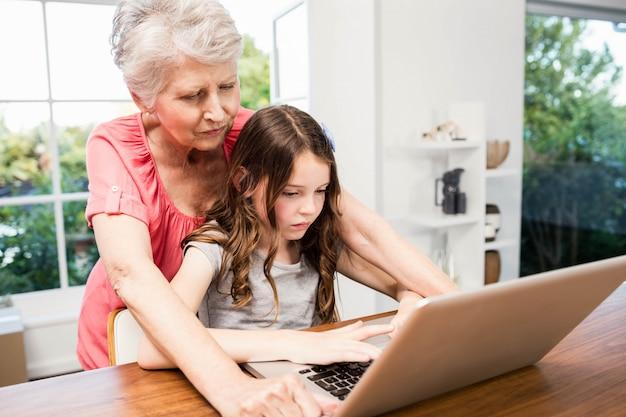 Porträt der lächelnden großmutter und der enkelin, die zu hause laptop verwendet