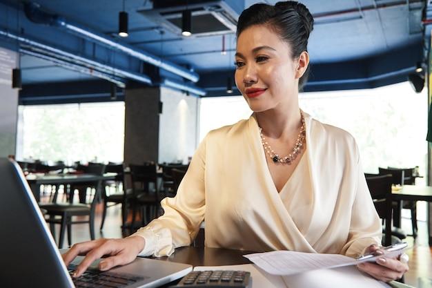 Porträt der lächelnden hübschen geschäftsfrau, die mit dokument arbeitet und daten auf laptop überprüft