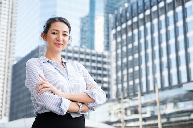Porträt der lächelnden hübschen jungen geschäftsfrau mit den armen verschränkt auf dem städtischen stadthintergrund des büros.